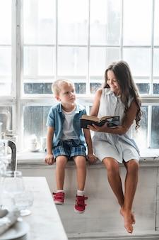 Jeune fille souriante montrant un livre à son petit frère assis près de la fenêtre
