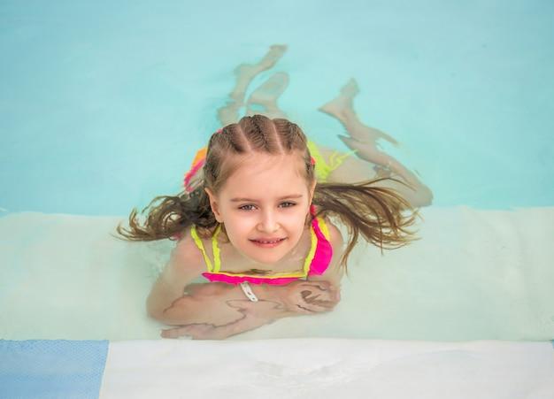 Jeune fille souriante nage au bord de la piscine