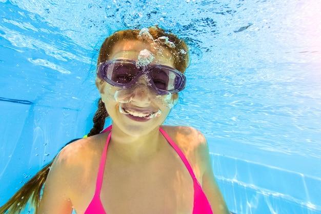 Jeune fille souriante, nager sous l'eau dans la piscine