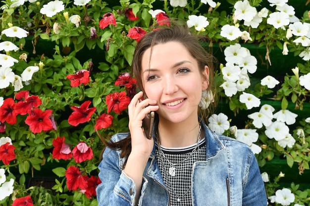 Jeune fille souriante parle sur l'espace des fleurs