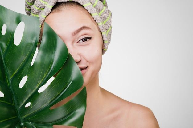 Une jeune fille souriante à la peau propre tient une feuille verte, sur la tête une serviette, un spa de jour