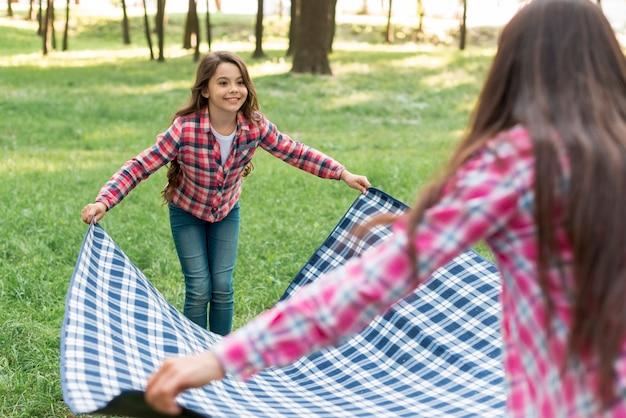 Jeune fille souriante, plaçant la couverture sur l'herbe avec sa mère