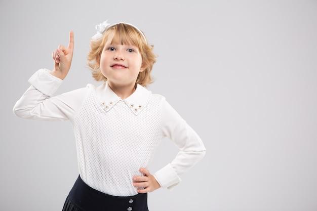 Une jeune fille souriante pointe son doigt sur l'espace libre. espace publicitaire. émotion vive.