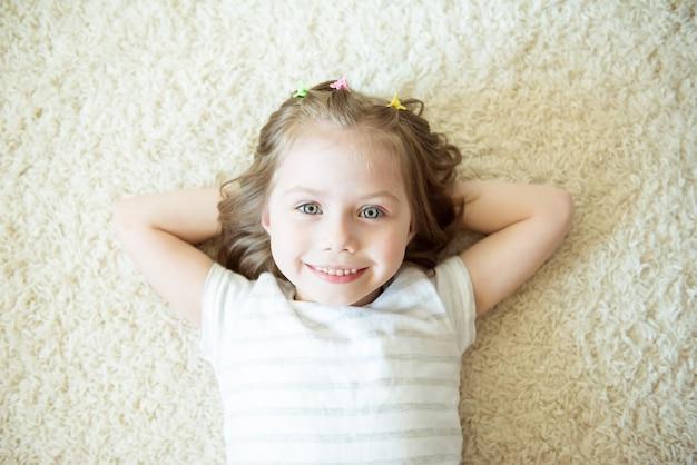 Jeune fille souriante sur un portrait de tapis blanc