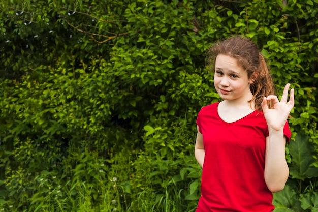 Jeune fille souriante posant et montrant un geste correct dans le parc