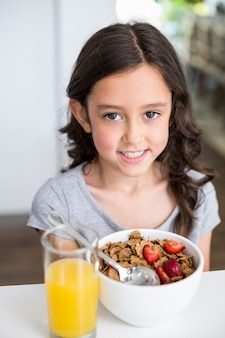 Jeune fille souriante prenant son petit déjeuner