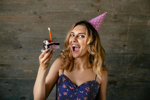 Jeune fille souriante prête à manger un morceau de gâteau au chocolat crème avec une bougie, portant un chapeau festif.