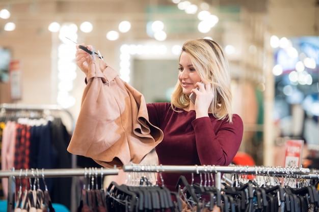 Jeune fille souriante à la recherche du bon short dans un centre commercial