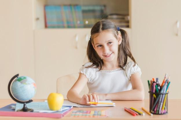 Jeune fille souriante regardant loin pendant la leçon