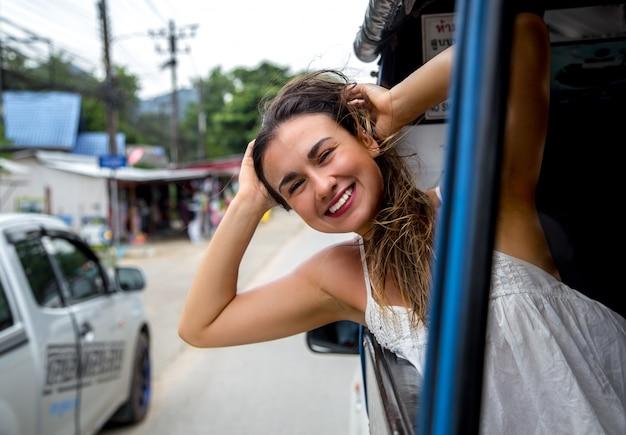 Jeune fille souriante regarde par la fenêtre d'un taxi, tuk-tuk
