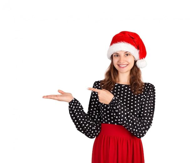 Jeune fille souriante en robe montre le doigt. fille émotive au chapeau de noël père noël isolé sur blanc. vacances