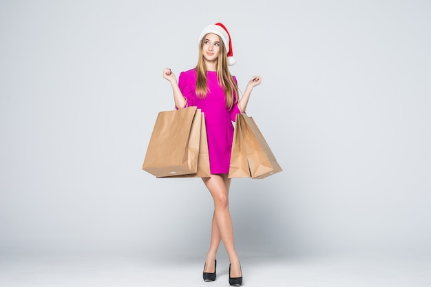 Jeune fille souriante en robe rose courte et talons chapeau de nouvel an tenir des sacs en papier isolés sur fond blanc