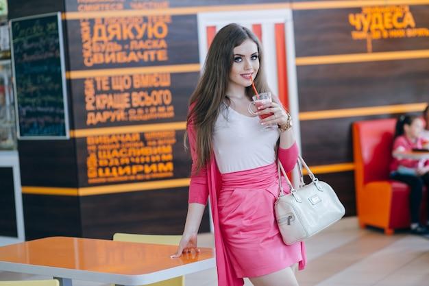 Jeune fille souriante avec un soda dans une main