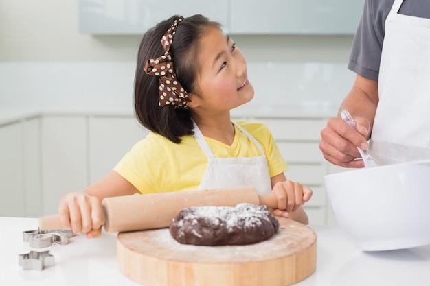 Jeune fille souriante avec son père prépare des biscuits dans la cuisine