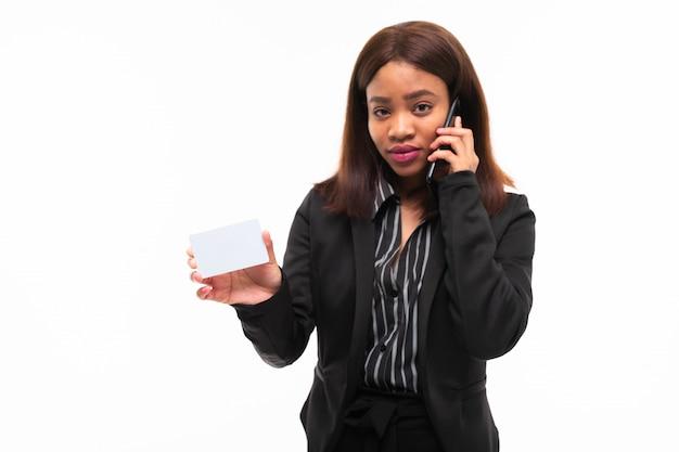 Jeune fille souriante souriante donnant une carte tout en parlant au téléphone isolé sur blanc