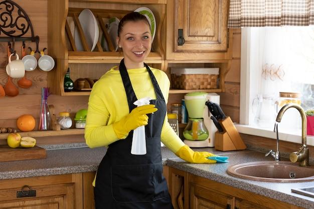 Jeune fille souriante en tablier noir essuie la surface de la cuisine avec un chiffon