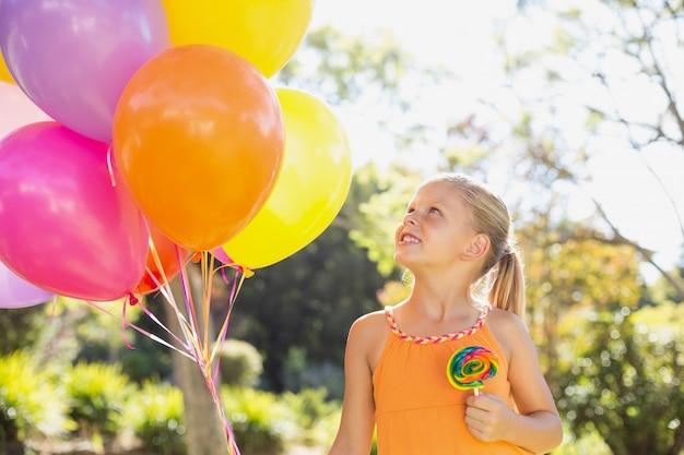 Jeune fille souriante tenant des ballons et sucette dans le parc
