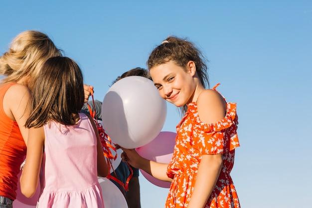 Jeune fille souriante tenant des ballons