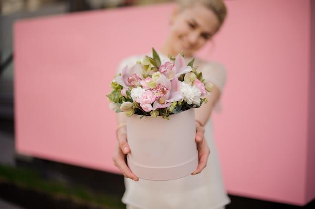 Jeune fille souriante tenant un bouquet dans une boîte à chapeau rose