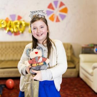 Jeune fille souriante tenant le cadeau d'anniversaire déballé