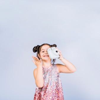 Jeune fille souriante tenant une caméra rétro instantanée devant elle un yeux sur fond bleu