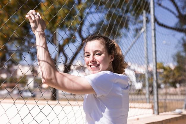 Jeune fille souriante tenant une clôture métallique