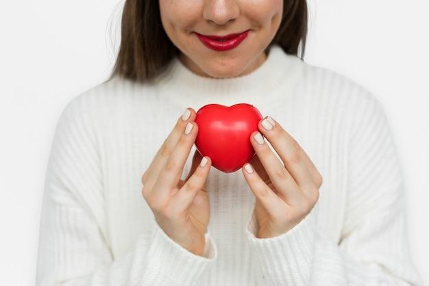 Jeune fille souriante tenant un coeur de res