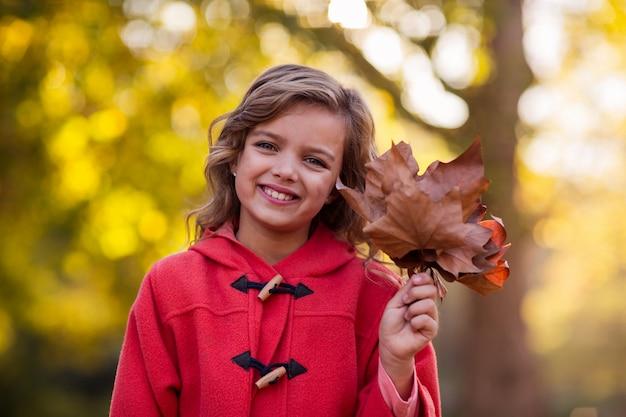 Jeune fille souriante tenant des feuilles d'automne au parc