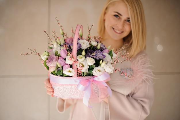 Jeune fille souriante tenant un panier de printemps de tendres fleurs blanches et violettes