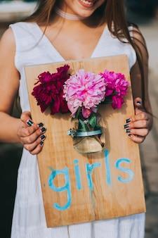 Jeune fille souriante tenant une planche de bois avec l'inscription filles et attachée à elle un bocal en verre avec des pivoines. décor et arrangement floral. belles fleurs printanières.