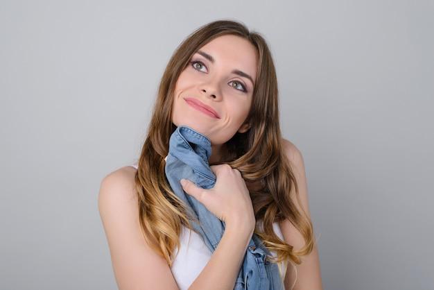 Jeune fille souriante tenant près de chemise de jeans poitrine isolé fond gris