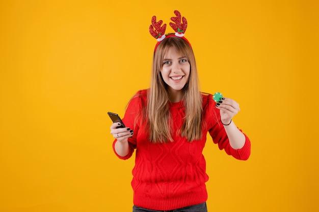 Jeune fille souriante tenant une puce de poker verte de casino en ligne et smartphone avec écran blanc