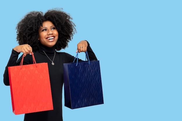 Jeune fille souriante tenant des sacs isolés sur fond bleu