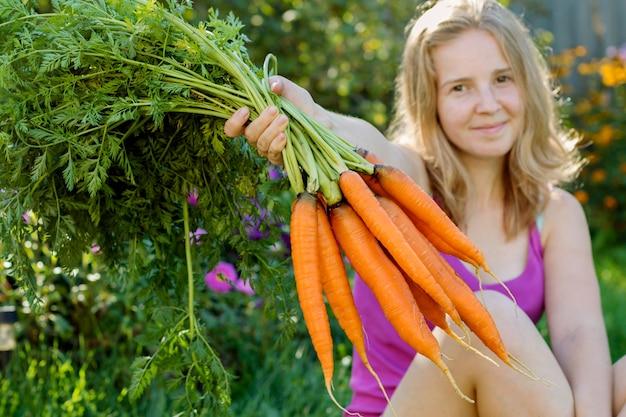 Jeune fille souriante tenant des tas de carottes.
