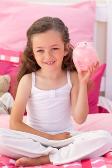 Jeune fille souriante tenant une tirelire