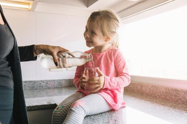 Jeune fille souriante tenant un verre pendant que sa mère verse de l'eau