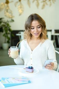Jeune fille souriante en tenue décontractée, défilement ou sms dans un smartphone tout en vous relaxant dans un café et en mangeant un délicieux gâteau au fromage