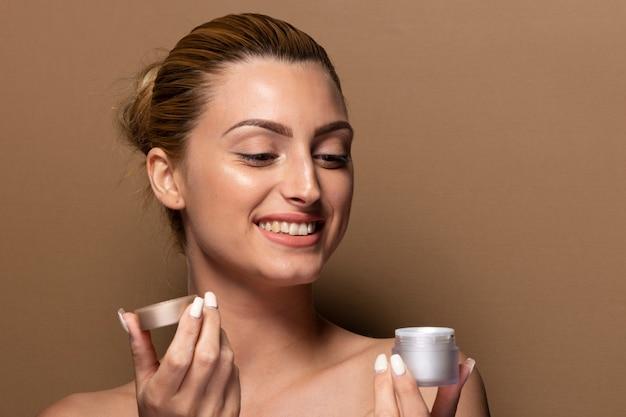 Jeune fille souriante teste des produits de soin de la peau