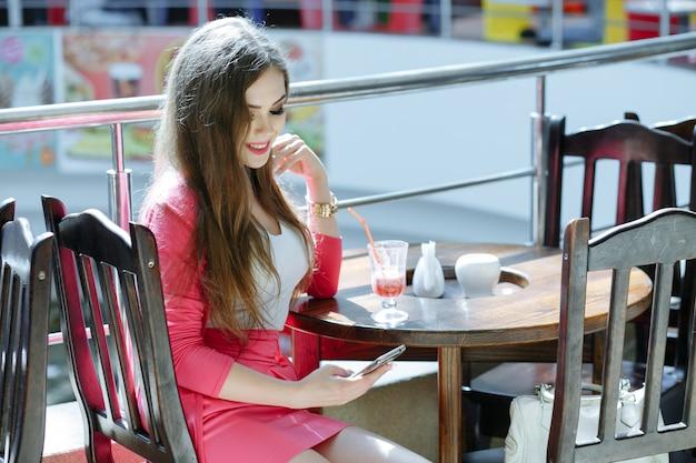 Jeune fille souriante tout en regardant son téléphone intelligent