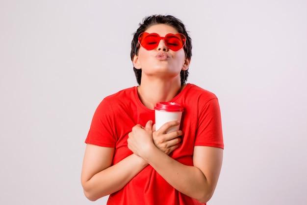 Jeune fille souriante avec un verre de café sur blanc