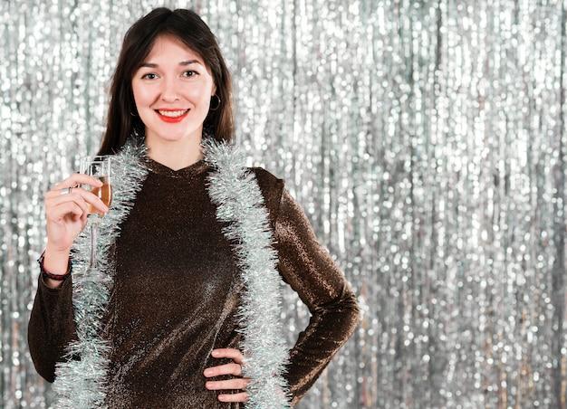 Jeune fille souriante avec un verre à la fête du nouvel an