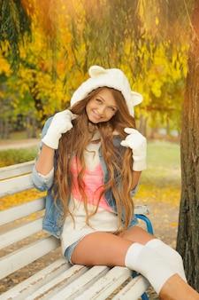 Jeune fille souriante vêtue d'un joli chapeau d'ours blanc tricoté dans un parc en automne.