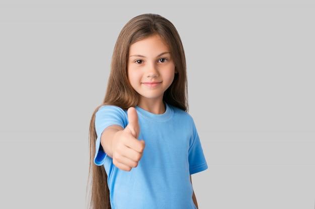 Jeune fille souriante vêtue d'un t-shirt bleu montrant un gros doigt