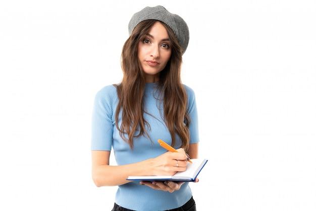 Jeune fille avec un sourire délicieux, de longs cheveux châtains ondulés, un beau maquillage, en jersey bleu, un jean noir, un béret gris, debout avec un carnet et un stylo