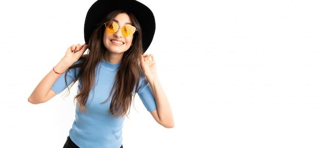 Jeune fille avec un sourire délicieux, de longs cheveux châtains ondulés, un beau maquillage, en jersey bleu, un jean noir, un béret gris, des lunettes, des supports de chapeau noir et des sourires