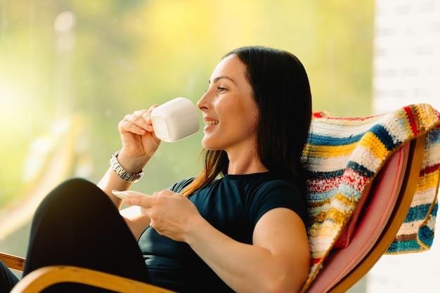 Jeune fille avec un sourire profite d'une journée parfaite assise dans un fauteuil à bascule avec une tasse de son café préféré.
