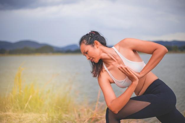 Jeune fille de sport faire du yoga dans le parc, femme de beauté asiatique