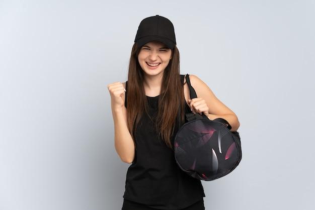 Jeune fille de sport avec sac de sport isolé sur gris célébrant une victoire en position de vainqueur