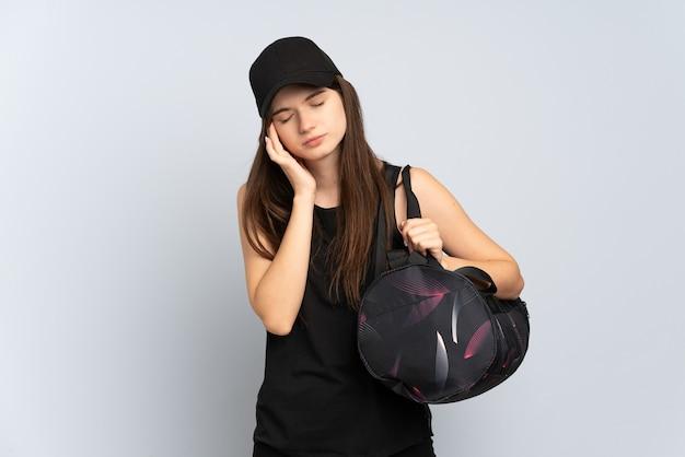 Jeune fille de sport avec sac de sport isolé sur gris avec maux de tête