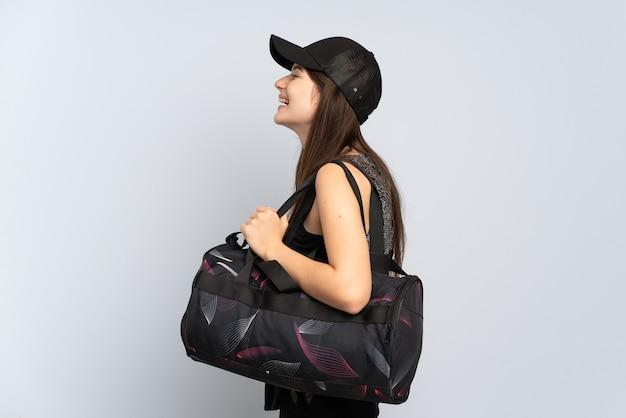 Jeune fille de sport avec sac de sport isolé sur gris rire en position latérale